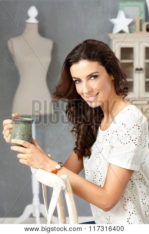 Happy young woman drinking tea in vintage home.