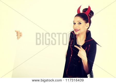 Woman in devil costume with empty banner.