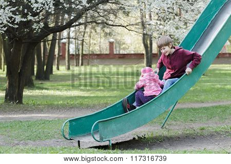 Sibling children sliding down on old park playground slide at blooming spring fruit tree background