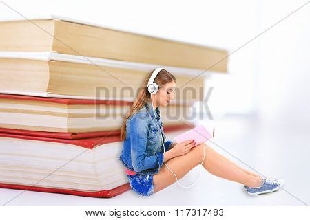 Beautiful young woman with headphones sitting near stack of books isolated on white