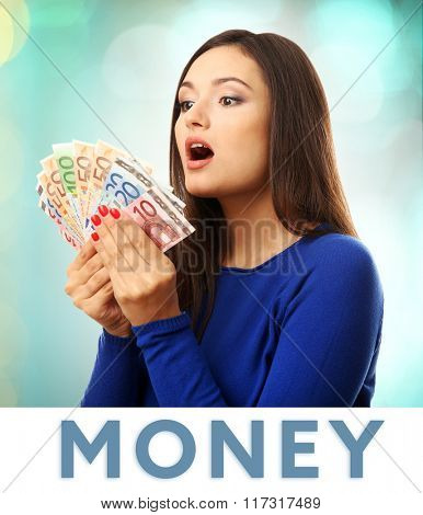 Woman holding money on bright background
