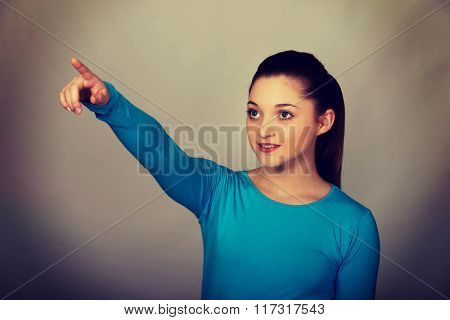 Smiling young woman pointing up.
