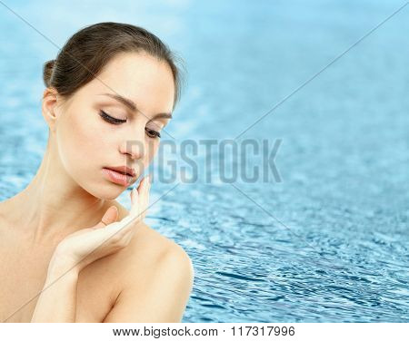 Beautiful young woman on water background
