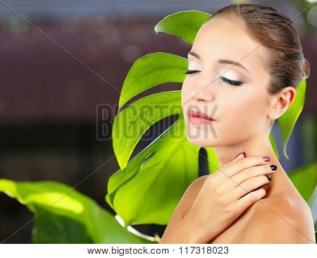 Beautiful young woman on big green leaf background