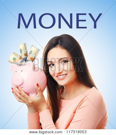 Woman with piggy bank and banknotes on blue background