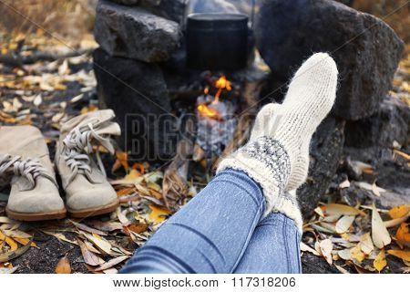 Female legs beside the fire