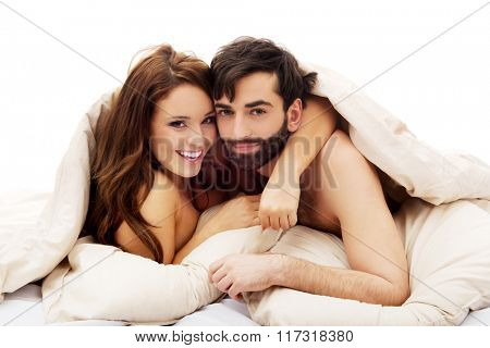 Beautiful couple under the cover in their bed.
