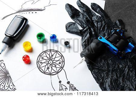 Tattoo machine, sketch and tattoo supplies on dark background