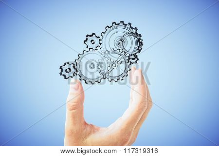 Man's Hand Shows The Mechanism Of Gears