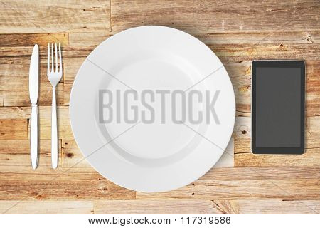 Plate And Cell Phone On A Wooden Table