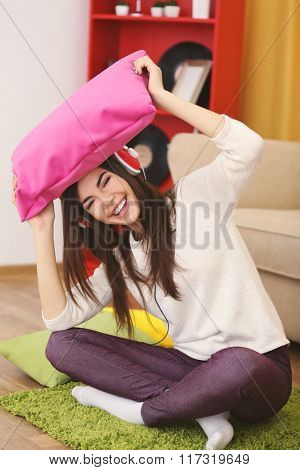 Happy young woman with headphones and pillow to listening music on a floor at home