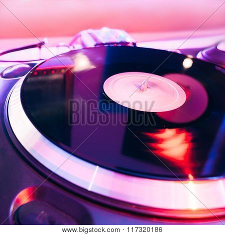 Turntable playing vinyl with club lighting