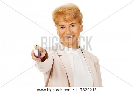 Smile elderly woman pointing at camera