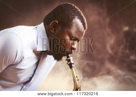 African American jazz musician playing the saxophone against smoky background