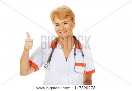 Smile elderly female doctor with stethoscope shows thumb up