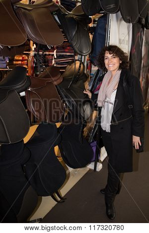 Woman  Contemplating Horse Saddle In The Store At Marketplace