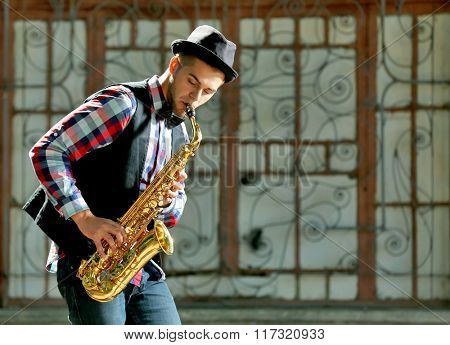 Man with saxophone outside near the brick wall