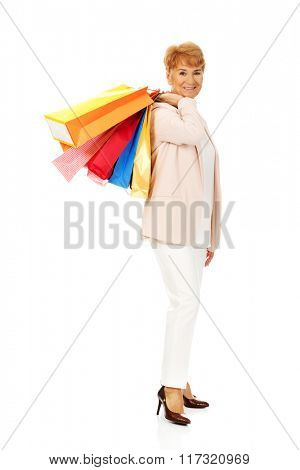 Happy elderly business woman holding shopping bags