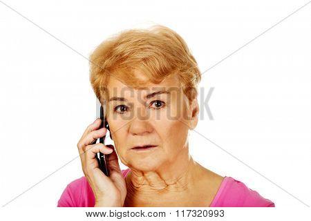 Worried senior woman talking through phone