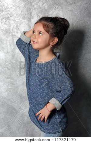 Portrait of little fashion kid girl on gray wall background