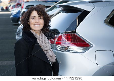 Successful Female Car Sales Representative. Happy Brunette Saleswoman Outdoor.