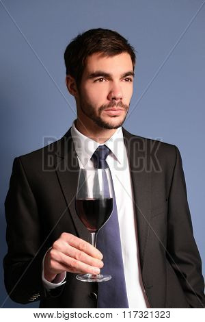 Man holding red wine in glass on blue background