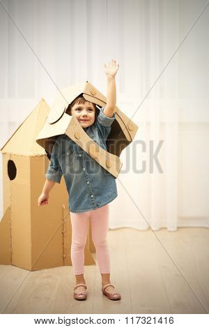 Little cute girl in astronaut helmet playing with cardboard space rocket in room