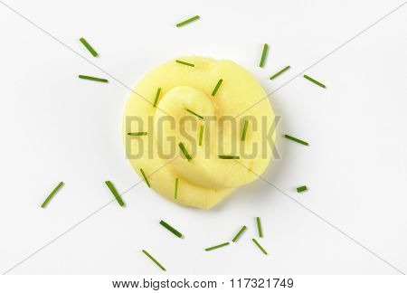 swirl of mashed potatoes with chives on white background