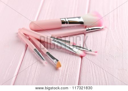 Makeup Brush Set On A Pink Wooden Background