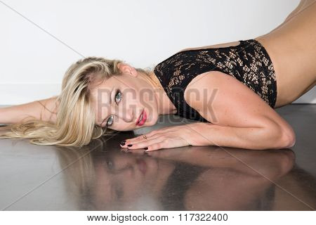 Sexy Blond  Woman In A Black Lingerie Lying On Floor