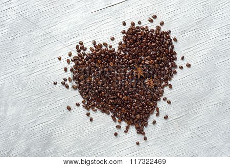 Heart shape made from coffee beans on wooden background