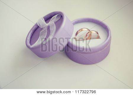 Wedding gold rings in the purple box on white background