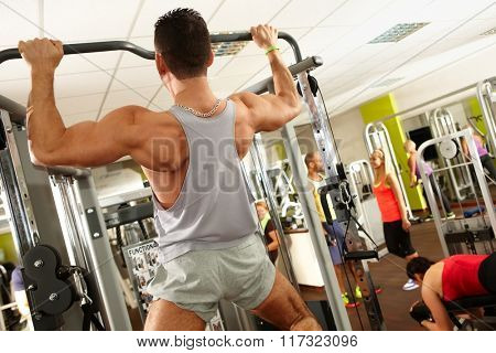 Muscular man training in gym, doing pull-up workout.