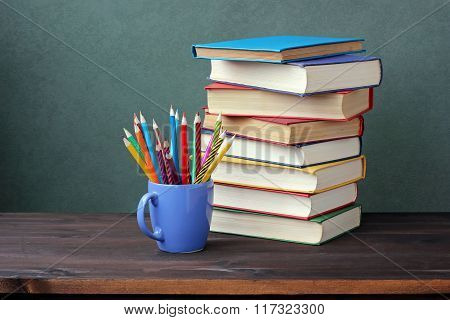 Pile Of Books With Color Covers And Colored Pencils In A Cup.