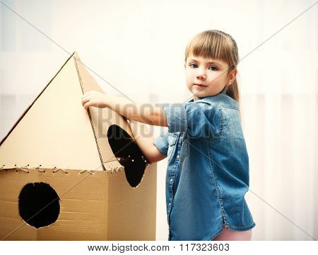 Little cute girl playing with cardboard space rocket in room
