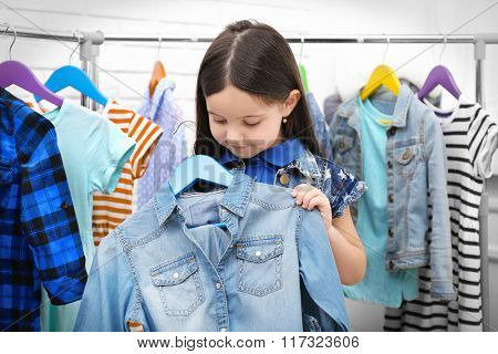 Little girl trying on a new jeans shirt