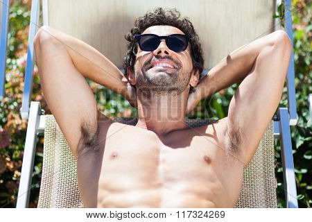Young Man Sunbathing By Pool
