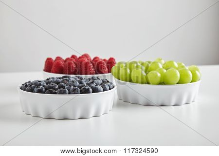 Heap Of Ripe Raspberries Blueberries Grapes In Ceramic Bowls