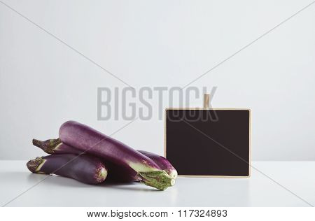 Heap Of Long Eggplants With Price Tag Isolated