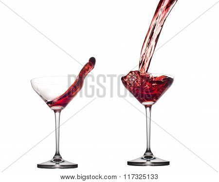 Red cocktail splashing from glass isolated on white background