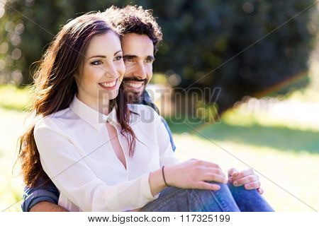 Happy young couple sitting on the grass