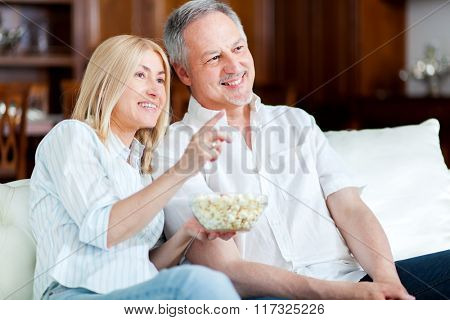 Couple eating pop-corn and watching tv