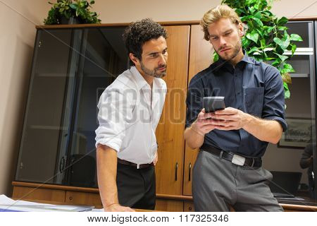 Businessman showing his mobile phone to a colleague