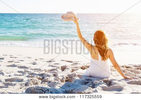 Young woman sitting on the beach