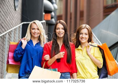 Portrait of three young happy beautiful women on street stairs with shopping bags.