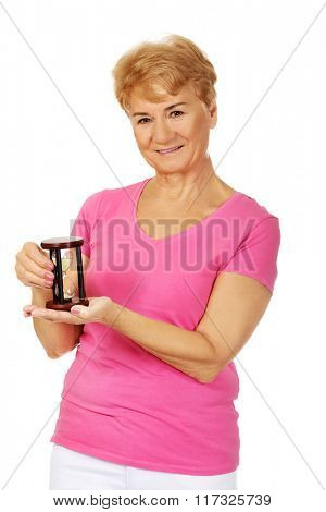 Smile senior woman holding sandglass