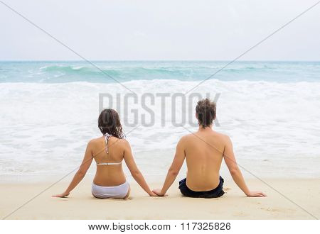 Young couple sitting on the beach. Back view.