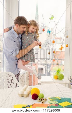 Cheerful father and her daughter painting and decorating easter eggs.
