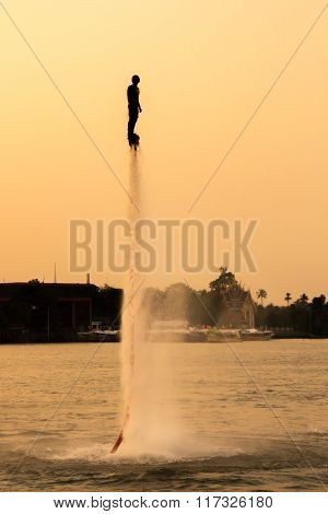 The new spectacular sport,Silhouette of a man showing the fly board in the river of Thailand