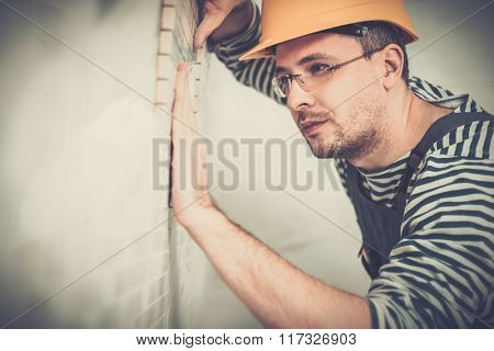 Builder applying tile on a wall